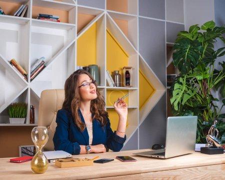 Photo pour Portrait d'une femme d'affaires prospère travaillant avec un ordinateur portable au bureau - image libre de droit