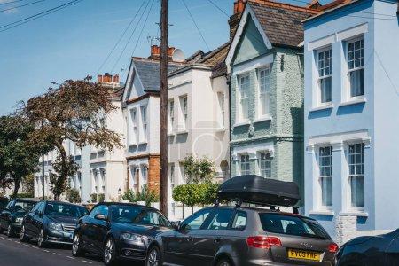 Foto de Londres, Reino Unido - 01 de agosto de 2018: Coches aparcados por casas de colores pastel colores en Barnes, Londres. Barnes es un área residencial afluente de Londres famoso para su atmósfera de pueblo - Imagen libre de derechos