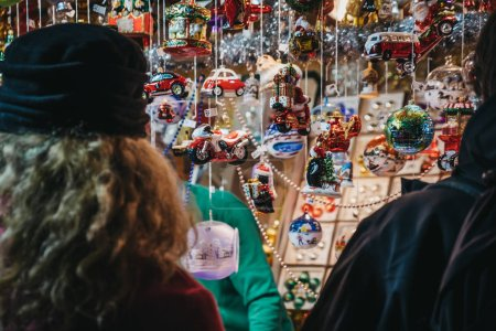 Rear view of unidentified people browsing Christmas decorations at Christmas World on Rathausplatz, traditional Christmas Market in Vienna with over 150 booths offering food, drinks and crafts.