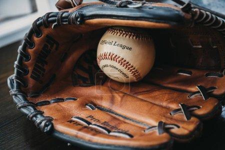 Photo pour Londres, Royaume-Uni - 3 janvier 2019 : Gros plan d'une balle de baseball blanche à l'intérieur d'un gant de baseball bronzé. Originaire d'Angleterre au XVIIIe siècle, le baseball est un sport très populaire dans de nombreux pays du monde . - image libre de droit
