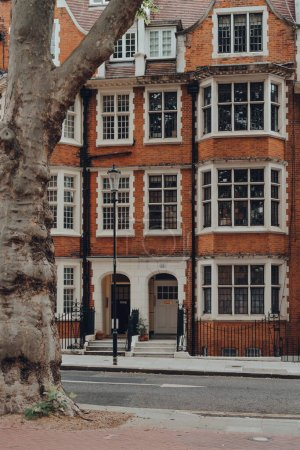 Photo for London, UK - June 20, 2020: Facade of red brick apartment block in Kensington, an affluent area of West London favoured by celebrities. Selective focus, framed by a tree. - Royalty Free Image