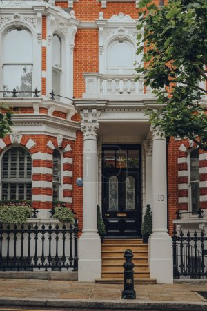 Photo for London, UK - June 20, 2020: Entrance of a traditional house with a stoop in Kensington, an affluent area of West London favoured by celebrities. Selective focus. - Royalty Free Image