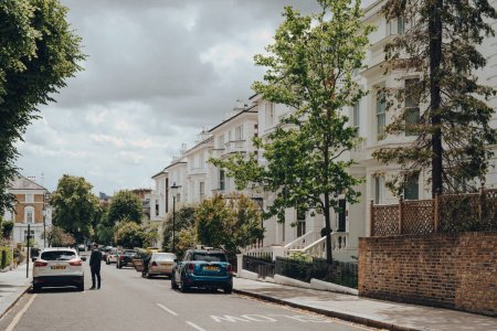 Photo for London, UK - June 20, 2020: Cars parked in front of white Victorian houses on a street in Holland park, an affluent area of West London favoured by celebrities. - Royalty Free Image