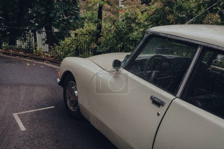 Photo for London, UK - July 02, 2020: Close up of retro car parked on a Hampstead street in the rain, selective focus. Hampstead is an affluent residential area of London favoured by artists and media figures. - Royalty Free Image