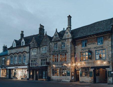 Photo pour Stow-on-the-Wold, Royaume-Uni - 6 juillet 2020 : L'extérieur du pub The Kings Arms et une rangée de magasins à Stow-on-the-Wold, une ville de marché à Cotswolds construit sur Roman Fosse Way, le soir. - image libre de droit