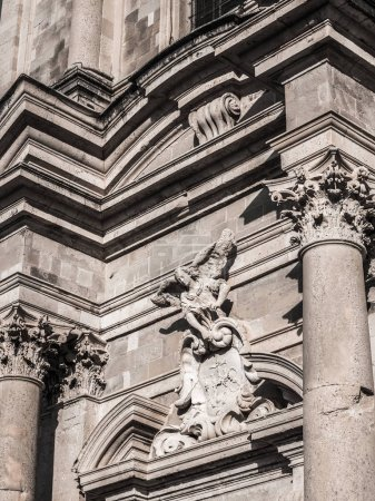 Close up detail and ornamentation photograph of the entrance and pediment over the door capped with an angel sculpture at  St. Ignatius Church in Old Town in Dubrovnik Croatia.