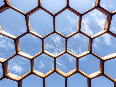 Photo for Beautiful view looking up at an intricate and delicate vaulted wood hexagonal wood architectural structure with repeating shape pattern with bright blue sky on a sunny day above. - Royalty Free Image