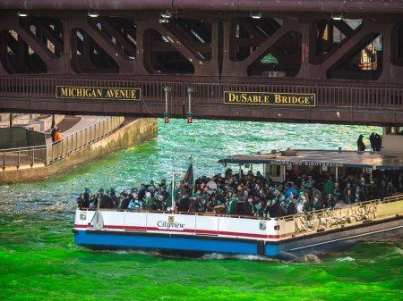 Foto de Chicago, Il-16 de marzo de 2019: grupos de personas montan en el barco Shoreline Sightseeing con una banda de gaita irlandesa a bordo como una tripulación vuelca tinte en el río y rocía agua verde vibrante en la parte posterior - Imagen libre de derechos