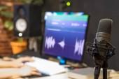 condenser microphone on sound engineer hands editing voice waveform background in broadcasting studio
