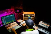 back of male asian producer working in sound design studio. music, film score, advertising footage digital editing, jingle song, voice actor recording, post production