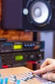 DJ, producer, composer, arranger hands adjusting sound mixer in recording, broadcasting studio