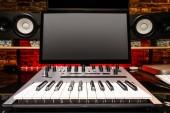 home studio. recording equipment, computer monitor, midi keyboard, analog synthesizer, studio loudspeakers monitor