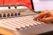 sound engineer fingers adjusting volume level fader on digital mixing console. music production, recording, broadcasting, music concept