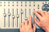 sound engineer hands adjusting volume level fader on digital mixing console. music production, recording, broadcasting, music concept