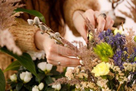 Photo pour Main féminine composant une composition de fleurs de bruyère. Le concept de tendresse. Gros plan . - image libre de droit