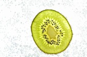 A sliced kiwi lies on a light background - through the thin kiwi slices are illuminated from below