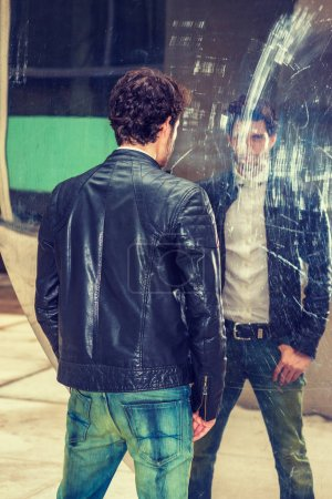 Mysterious Man looking at mirror. A young handsome guy with beard, standing by metal mirror wall, looking at the reflection, thinking. Concept of self assured, self esteem, self checking strategies.