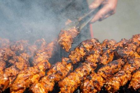 Photo pour Viande sur brochettes frites sur le gril en plein air, mains visibles du cuisinier . - image libre de droit