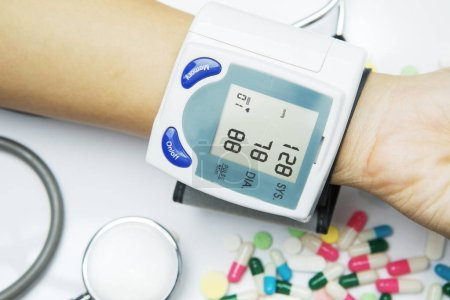 Photo pour Gros plan d'une femme inconnue vérifiant la pression artérielle et la fréquence cardiaque à l'aide d'un tensiomètre numérique - image libre de droit