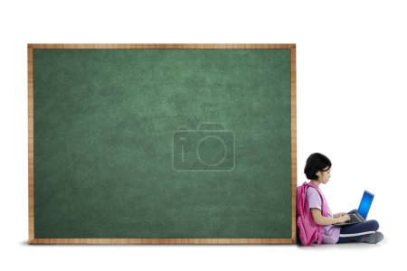 Photo for Picture of cute schoolgirl using a laptop while sitting with a blank chalkboard, isolated on white background - Royalty Free Image