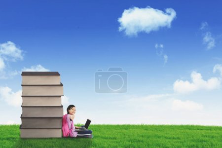 Photo for Image of happy schoolgirl showing thumb up while using a laptop and sitting near a pile of books in the meadow - Royalty Free Image