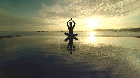 Photo pour Silhouette d'une femme inconnue méditant sur la plage tout en faisant du yoga au coucher du soleil. Tourné à Lombok, Indonésie - image libre de droit