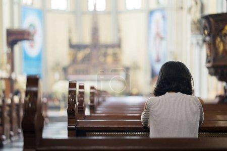 Photo pour Vue arrière de la religieuse priant DIEU alors qu'elle était assise dans l'église - image libre de droit