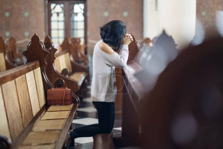 Photo for Side view of young woman sitting with clasped hands in the church while praying to GOD - Royalty Free Image
