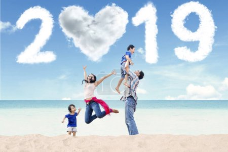 Photo for Portrait of Asian family having fun in the beach with clouds shaped heart and numbers 2019 in the sky - Royalty Free Image