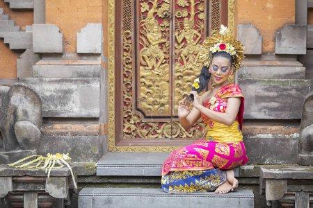 Photo pour Belle jeune femme balinaise assise dans une porte de temple tout en portant des vêtements traditionnels - image libre de droit
