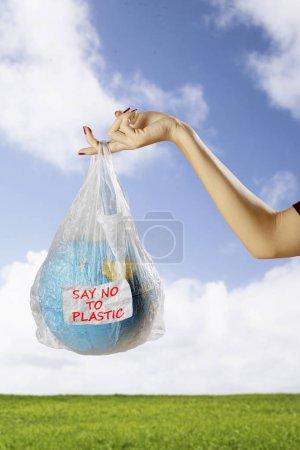 Primer plano de la hembra sostiene un globo terráqueo en una bolsa de plástico con texto de decir no al plástico. Disparo en el prado