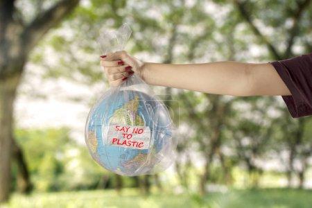 Photo pour Concept de sauver la terre de la pollution par les déchets plastiques. Jeune femme avec globe terrestre dans un sac en plastique et texte de dire non au plastique - image libre de droit