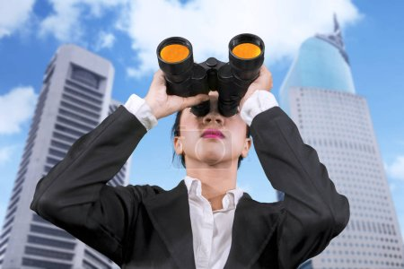 Low angle view of young businesswoman using binoculars while standing in skyscraper background