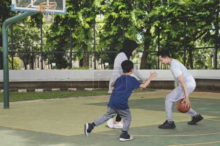 Photo for Picture of young Muslim family playing basketball while having fun in the field - Royalty Free Image