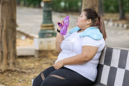 Photo for Overweight woman drinks mineral water with bottle after exercising at the park - Royalty Free Image