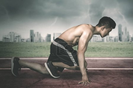 Photo pour Vue latérale d'un jeune homme musclé prêt à courir en s'agenouillant sur la piste - image libre de droit