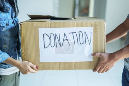 Photo pour Gros plan d'une jeune femme qui donne une boîte de dons à un bénévole masculin à l'orphelinat - image libre de droit