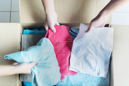 Photo pour Mains de trois personnes qui mettent des vêtements dans une boîte en carton. Concept de don - image libre de droit