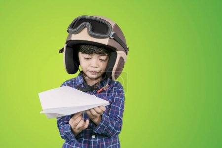 Photo for Picture of little boy wearing helmet while holding a paper plane and standing in the studio - Royalty Free Image