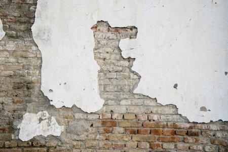 Photo pour Gros plan de plâtre blanc endommagé sur un mur de briques rouges - image libre de droit