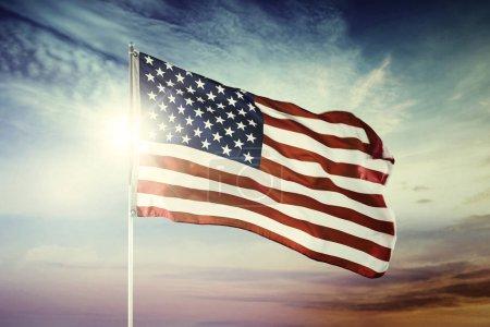 Photo pour Image du drapeau américain soufflant dans un vent avec un arrière-plan du lever du soleil à l'aube - image libre de droit