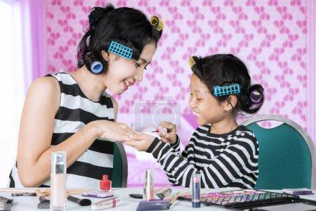 Photo pour Joyeux enfant qui applique du vernis à ongles sur sa mère tout en faisant du maquillage ensemble dans la chambre à coucher. - image libre de droit