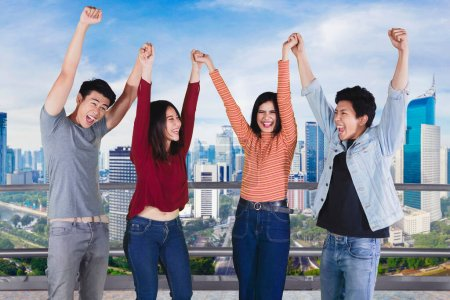 Photo for Group of happy people lifting hands together to celebrating their success on the rooftop with skyscrapers background - Royalty Free Image