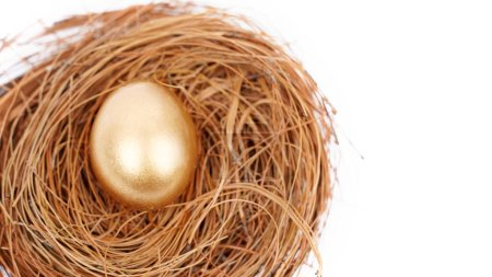 Blick von oben auf das goldglänzende Ei auf dem Strohnest mit Kopierraum. Isoliert auf weißem Hintergrund