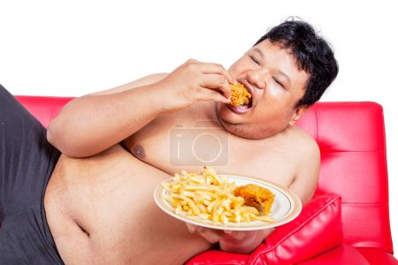 Close up of an obesity man eating junk foods while lying on the couch. Shot in the studio with isolated on white background