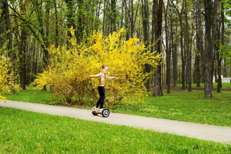 girl in a gold jacket rides whirl on a hoverboard over park paths