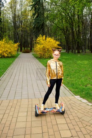 a girl in a gold jacket stands on self balancing scooter in the park