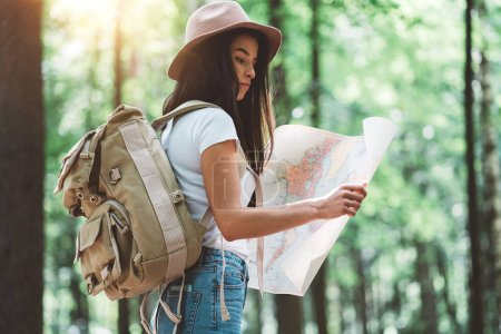 Photo for Traveler hipster woman with backpack and hat hold in hands location map and searching directional among trees in forest. Flare effect - Royalty Free Image