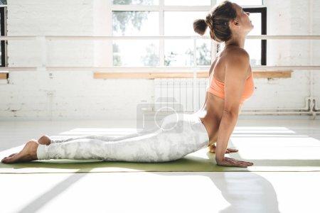 Photo pour Portrait de jeune femme en forme pratiquant le yoga en classe blanche intérieure. belle fille pratique cobra asana dans sunny gym - image libre de droit