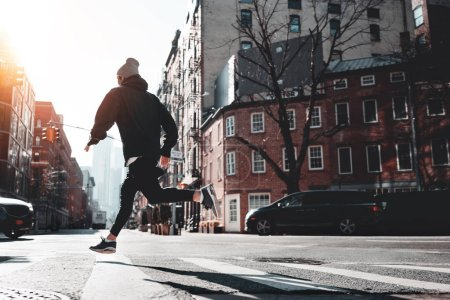 Photo for Urban male athlete running on asphalt through the New-York streets. Fast man runner wearing sportswear preparing for marathon - Royalty Free Image